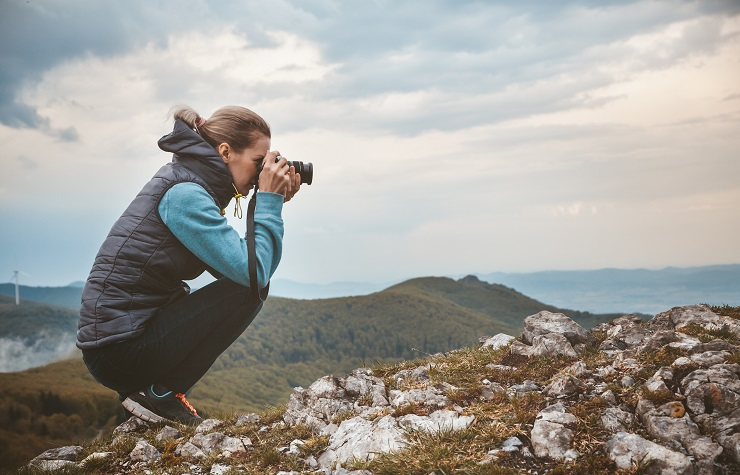 Woman photographer taking picture on hilltop.